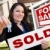 hispanic woman holding sold real estate sign and keys in front h stock photo © feverpitch