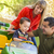 young mixed race boy enjoys toy tractor with parents stock photo © feverpitch