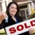 hispanic woman holding keys and sold sign in front of house stock photo © feverpitch