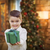 Mixed Race Boy with Christmas Tree Handing Gift Out Front stock photo © feverpitch