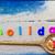 word holiday laid sand blue board stock photo © fotoaloja