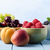 fresh fruit choices in bowls on light blue wood planked table stock photo © frannyanne