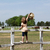 little girl with hat in hand standing on a corral fence stock photo © goce