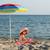 happy little girl sitting under sunshade on beach stock photo © goce