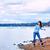 teen girl throwing rocks in the water along a rocky lake shore stock photo © jarenwicklund