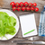 fresh healthy salad tomatoes water bottle and notepad for copy stock photo © karandaev