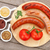 various grilled sausages with condiments and tomatoes stock photo © karandaev