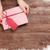 female hands holding gift above wooden table stock photo © karandaev
