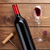 red wine bottle glass and corkscrew on wooden table stock photo © karandaev