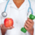 doctor woman hands with dumbbell and apple stock photo © kurhan