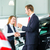 young woman and seller with auto in car dealership stock photo © kzenon