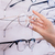 woman taking glasses out of shelf in optician store stock photo © kzenon