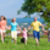 father with children running on green meadow grass stock photo © kzenon