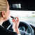 woman using lipstick while driving her car stock photo © kzenon