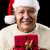 aged man with santa claus cap and red xmas gift stock photo © leowolfert