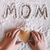 partial top view of child holding heart shaped cookie and word mom written in flour mothers day co stock photo © lightfieldstudios