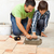 boy learning how to spread adhesive for ceramic floor tiles stock photo © lightkeeper