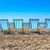 4 deck chairs on a pebble beach stock photo © lucielang