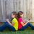 twin sister girls playing smartphone sitting on backyard lawn stock photo © lunamarina