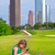 blond kid girl playing with smartphone sitting on park lawn at c stock photo © lunamarina