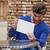 young man using tablet pc as a mirror fixing hair stock photo © lunamarina