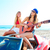 girls having fun playing guitar on th beach in a car stock photo © lunamarina