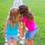 friends sister girls whispering secret in ear in garden stock photo © lunamarina