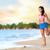 happy woman doing stretching exercise on beach stock photo © maridav