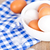 eggs in a bowl, towel and feathers on rustic wooden table stock photo © marylooo