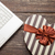 photo of cute wrapped gift and laptop on the wonderful brown woo stock photo © massonforstock
