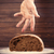 male hand under bread loaf on the wonderful brown wooden backgro stock photo © massonforstock