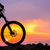 professional cyclist resting with down hill bike on the rock at sunset stock photo © maxpro