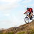 cyclist in red jacket riding the bike down rocky hill extreme sport stock photo © maxpro