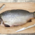 a large fresh carp live fish lying on a wooden board with a knife stock photo © mcherevan
