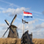 old windmill with the netherlands flag white clouds on a blue sky the wind is blowing stock photo © mcherevan