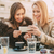 glimlachend · vrienden · vergadering · cafe · naar · telefoon - stockfoto © milanmarkovic78