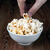 bowl filled with salt popcorn on a wooden table and human hand stock photo © mizar_21984