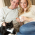 Young couple sitting with cat on sofa with cup in hand stock photo © monkey_business