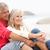 senior couple on holiday sitting on winter beach stock photo © monkey_business