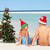 boy and girl sitting on beach with christmas tree and hat stock photo © monkey_business