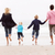 back view of young family running along winter beach stock photo © monkey_business