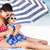 mother and daughter under beach umbrella putting on sun cream stock photo © monkey_business