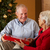 senior couple exchanging gifts in front of christmas tree stock photo © monkey_business