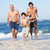grandfather father and grandson running along beach stock photo © monkey_business