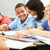 teacher helping pupils studying at desks in classroom stock photo © monkey_business