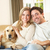 Young happy couple with dog sitting on sofa stock photo © monkey_business
