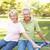 senior couple riding on roundabout in park stock photo © monkey_business