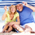 senior couple sheltering from sun under beach umbrella stock photo © monkey_business
