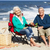 senior couple sitting on beach in deckchairs having picnic stock photo © monkey_business