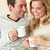 Young couple sitting and relaxing on sofa with cup in hand stock photo © monkey_business